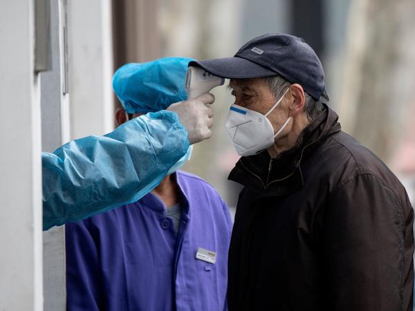 A man wearing a face mask has his temperature checked before entering a community hospital in Shanghai on Thursday. China's official death toll and infection numbers from the deadly COVID-19 coronavirus spiked dramatically on Thursday after authorities changed their counting methods.