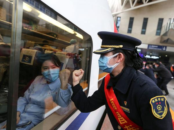 A Chinese train attendant and medical worker gesture to each other, as the train prepares to depart for the city of Wuhan, the epicenter of the novel coronavirus outbreak.