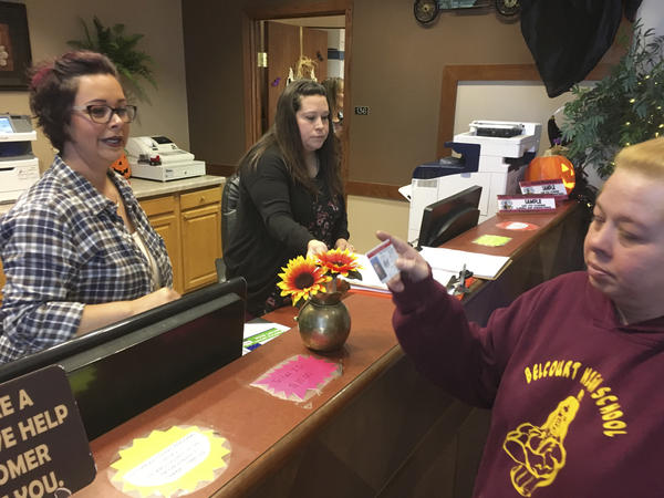 Delaine Belgarde (right) shows the new Turtle Mountain Band of Chippewa identification card, in Belcourt, N.D., in 2018.