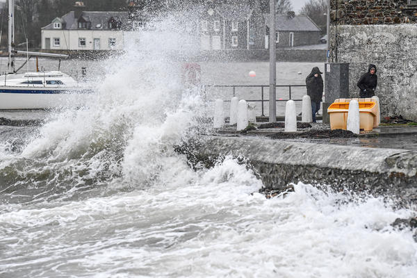 Waves crash against the harbor wall on Saturday in Isle of Whithorn, U.K.