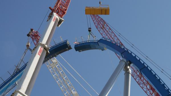 Lift Element #11, the lift hill's keystone, is lifted into place while the crew waits overhead to bolt both sides together.