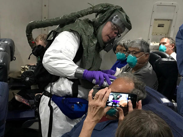 Checking for signs of COVID-19, a medical worker in a protective suit checks the temperatures of people who were on board the Diamond Princess cruise ship as they fly on a chartered evacuation plane from Japan to Lackland Air Force Base in Texas.
