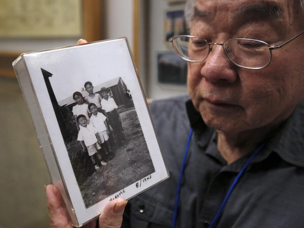 During a visit last week to the California Museum in Sacramento, Les Ouchida holds a 1943 photo of himself (front row center) and his siblings taken at the internment camp in Jerome, Ark., that his family was moved to from their home near Sacramento in 1942.