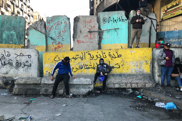 Protesters near Baghdad's Tahrir Square. The concrete barriers have been erected by security forces who are trying to prevent demonstrations from moving closer to Baghdad's fortified Green Zone.