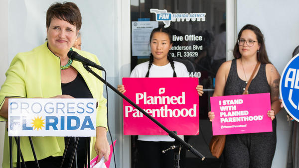 Abortion rights activists pose outside of Rep. Jackie Toledo's office after voicing dissent to the bill requiring parental consent before minors get abortions on Thursday, Feb. 20.