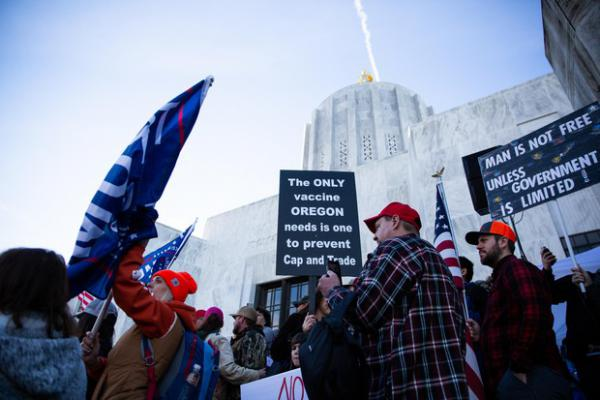 People hold signs at a Timber Unity rally in front of the Oregon Capitol in Salem, Ore., Thursday, Feb. 6, 2020. The group is opposing cap-and-trade legislation aimed at reducing greenhouse gas emissions.