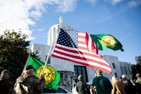 Men raise United States and State of Jefferson flags outside the Capitol in Salem, Ore., during a Timber Unity rally Thursday, Feb. 8, 2020. Timber Unity's signature issue is opposition to cap and trade, a plan to reduce greenhouse gas emissions, but the group attracts others like climate change deniers and State of Jefferson secessionists.