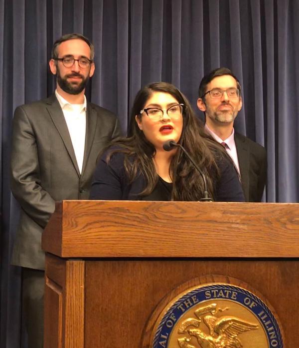 Graciela Guzman speaking about rising prescription drugs alongside (left) State Representative Will Guzzardi and (right) Dan Rabbitt of Heartland Alliance.