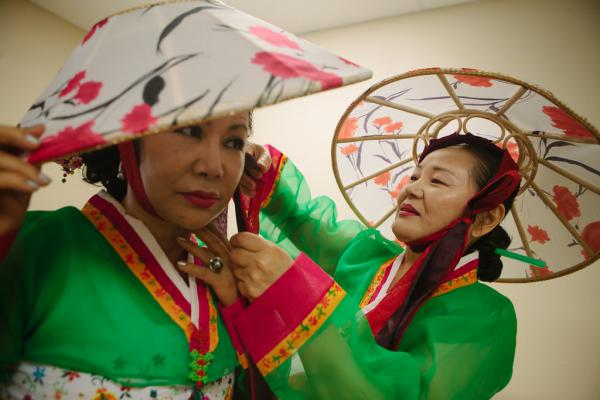 Connie Kim adjusts the hair of Kyong Ah before they take the stage to perform Uh Woo Dong, a traditional Korean dance. The Korean United Pentecostal Church hosts a Parents' Day celebration in 2014 for the parents and senior citizens of the community.