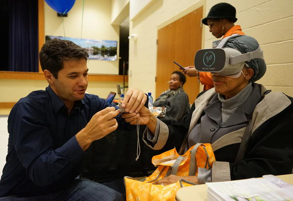 Climate researcher Juliano Calil helps a resident of Turner Station use the virtual reality program he created to show the expected impacts of sea level rise there.