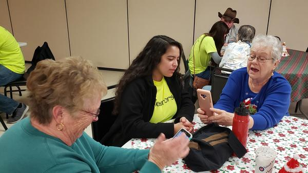 Kendra Gonzales coaches Linda Haverty on how to add a photo of a friend to her contacts list on her phone.