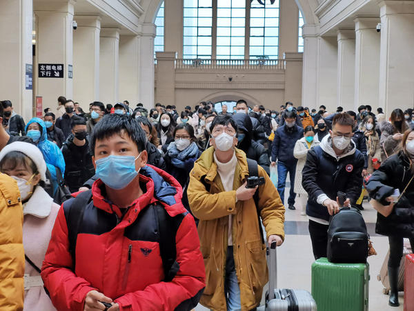 People wear face masks as they wait at Hankou Railway Station earlier this week in Wuhan, China. Experts say there is little evidence that masks prevent infection.