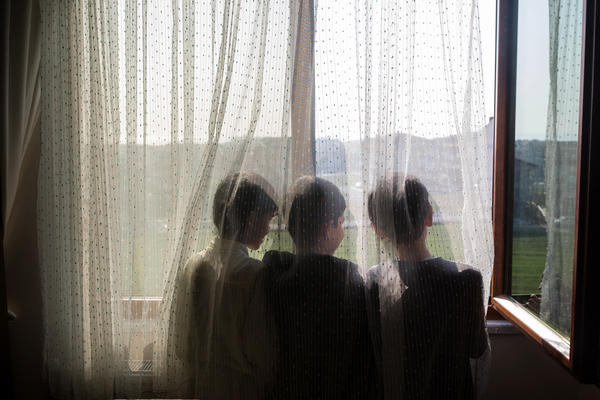 Ten-year-old Nurzat (right) and his friends, brothers Abdulla (left), 11, and Muhammet (center), 10, look out the window of their dormitory room at a boarding school in Istanbul, Turkey. The boys are all missing their parents, who are believed to be in prison camps in China.