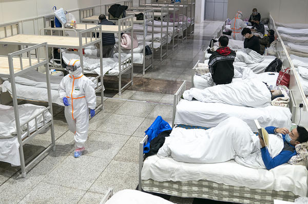 Coronavirus patients settle down in a large temporary hospital built two days ago in an exhibition center in Wuhan in central China's Hubei province. At another area hospital, a doctor who gave an early warning on social media about the virus has died.