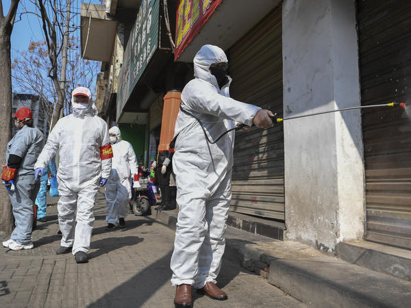 Workers disinfect closed shop lots following the coronavirus outbreak in Hubei, China, on Monday. Officials reported on Tuesday that the country's overall death toll had passed 1,000.