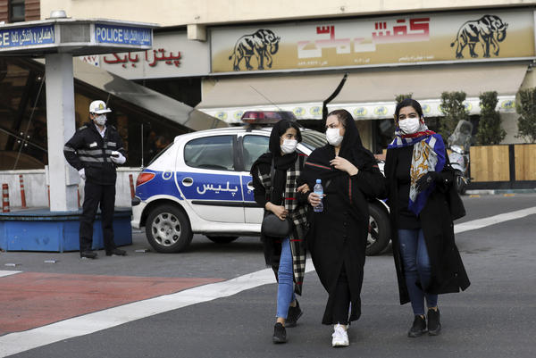 In downtown Tehran, Iran, on Sunday, a policeman and pedestrians wear masks to help guard against the coronavirus.