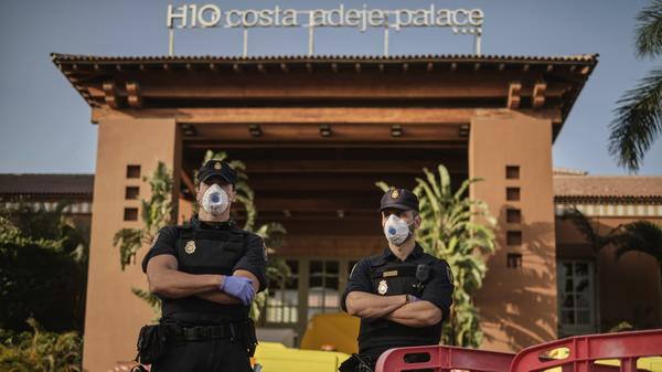 Police officers wear face masks Wednesday in front of a hotel on Tenerife, the largest of Spain's Canary Islands. Spanish officials say a hotel on the island has been placed under quarantine after an Italian doctor staying there tested positive for the new coronavirus.