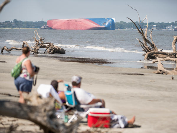 People watch from Jekyll Island as emergency responders work to rescue crew members from a 656-ft. capsized cargo ship on Sept. 9, 2019 in St. Simons Island Sound, Brunswick, Ga.