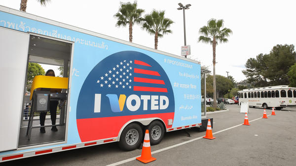 """A voter prepares her ballot during early voting for the California presidential primary election at a new LA County """"Mobile Vote Center"""" outside Universal Studios Hollywood on Thursday. Large numbers of Californians vote early and by mail, which can slow election night vote counting."""