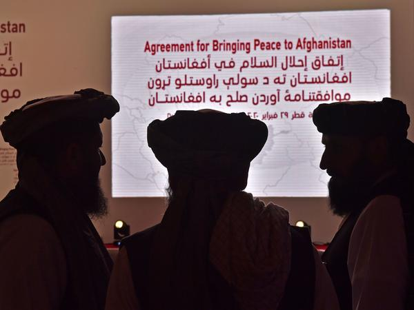 Members of the Taliban delegation gather ahead of Saturday's signing ceremony with the United States in the Qatari capital of Doha.