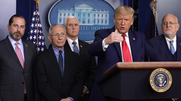 Surrounded by officials, including Vice President Mike Pence, President Trump speaks Saturday afternoon from the White Hosue about the administration's coronavirus response.
