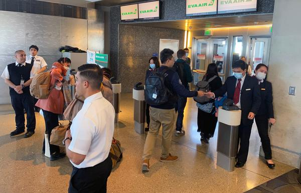 Humans — workers and flight crews as well as passengers — can be exposed to any number of pathogens at airports. EVA Air employees are seen wearing face masks at the Los Angeles airport in February amid the coronavirus outbreak. U.S. officials advise masks are not the best way to mitigate one's risk of contracting the virus.