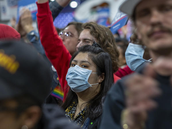 A woman in California wears a medical mask during a political campaign rally. A second person has died from COVID-19 in the U.S., officials in Washington state say.
