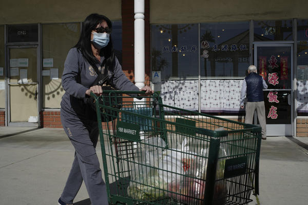 Tien Ngyuen wears a mask as she shops at the 168 Market in Alhambra, Calif., Friday, Jan. 31, 2020.