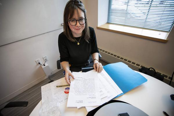 Eliza Mulcahy opens a folder with letters to her pen pal in prison, whose preferred candidate is Bernie Sanders.  (Jesse Costa/WBUR)