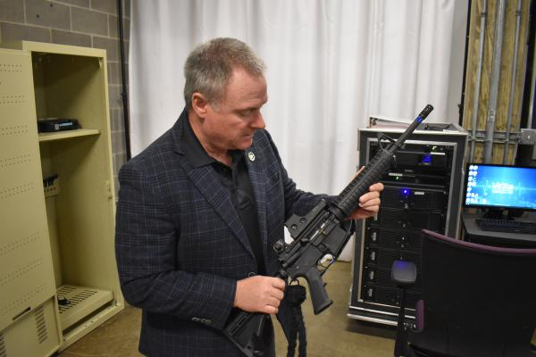 Brian Fengel, director of the Central Illinois Police Training Center, holds a VR rifle used with the VirTra police training simulator.
