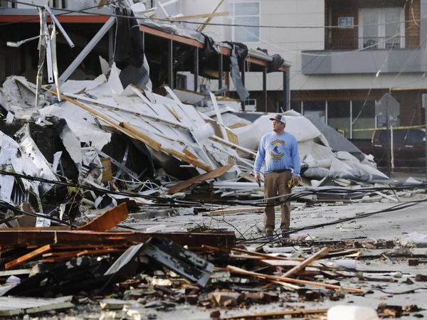 A man looks over buildings destroyed by storms on Tuesday in Nashville, Tenn. Tornadoes ripped across the state early Tuesday, shredding infrastructure and killing multiple people.