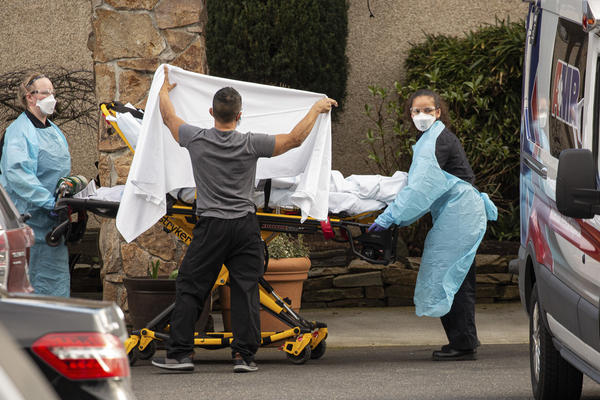 Health care workers bring a patient into an ambulance at Life Care Center in Kirkland, Wash. Two deceased residents of the eldercare facility had posthumous diagnoses of COVID-19, the disease caused by the new coronavirus.