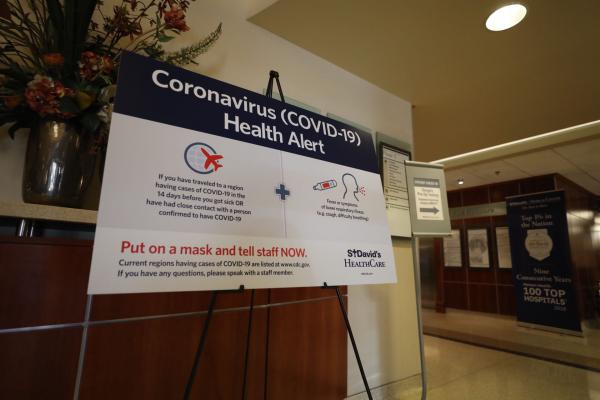 A sign telling visitors at St. David's Medical Center to alert staff if they've traveled to a region with cases of COVID-19 and have certain respiratory symptoms.