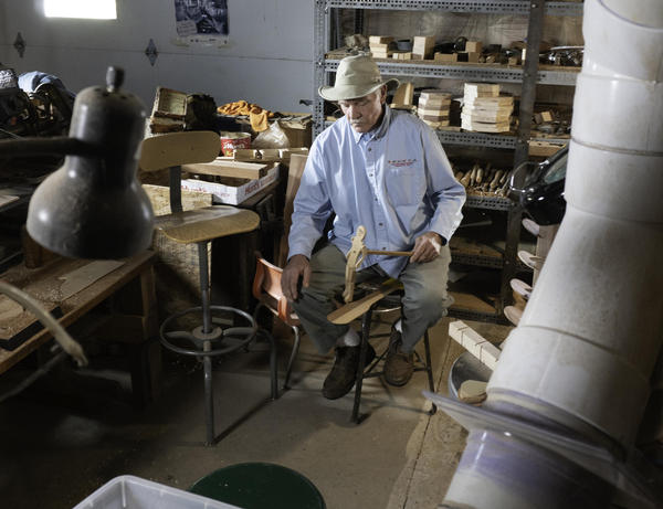 """Steve Conlon demonstrates the traditional """"limber jack"""" dancing toy in his workshop."""