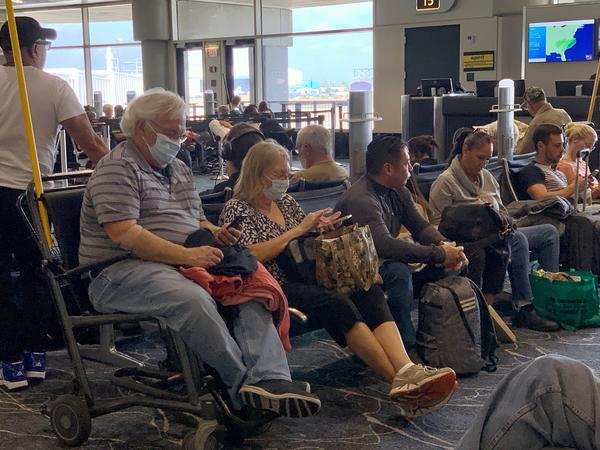 Travelers at Tampa International Airport don facemasks in reaction to the Coronavirus outbreak.
