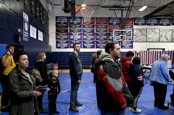 Jonathan Alvin, 26, of White River Junction, Vermont, at center, is in line to vote at the Hartford High School on March 3, 2020, in White River Junction.