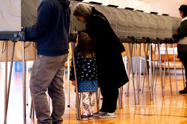 "Courtney Enos-Robertson is watched by her daughter Oswin, 4 (or ""Winnie"" as she is  called), as she votes on Super Tuesday at the Kittery Community Center on March 3, 2020, in Kittery, Maine."