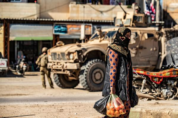A woman carrying produce walks past a US military armoured vehicle in the town of Tal Tamr along the M4 highway in the northeastern Syrian Hasakeh province, near the border with Turkey, on March 3, 2020. (DELIL SOULEIMAN/AFP via Getty Images)