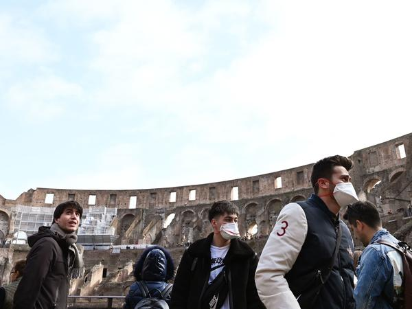 Tourists wearing respiratory masks visit the Coliseum in Rome on Friday. Italy's coronavirus cases have continued to rise, making it one of the hardest-hit countries.