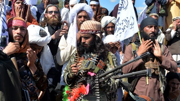 Afghan Taliban militants and villagers celebrate the U.S. peace deal Monday in the Alingar district of Laghman Province. The group resumed offensive operations against Afghan security forces this week, ending a partial truce.