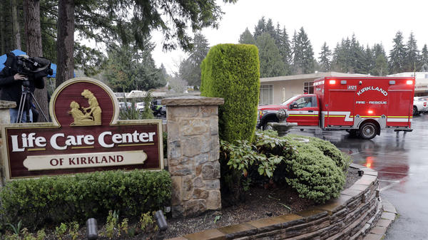 An ambulance backs into a parking lot on Friday at the Life Care Center in Kirkland, Wash., which has become the epicenter of the coronavirus outbreak in Washington state.