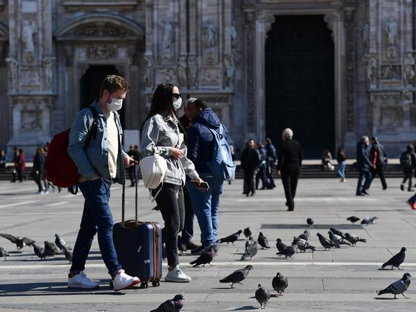 Tourists walk at the Piazza del Duomo in central Milan on March 8, after millions of people were placed under forced quarantine in northern Italy.