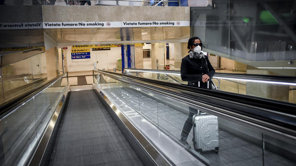 A woman wearing a medical mask rides an escalator at Milan Central train station on Sunday after Italy's government restricted much of the country in an effort to stanch the spread of the coronavirus.