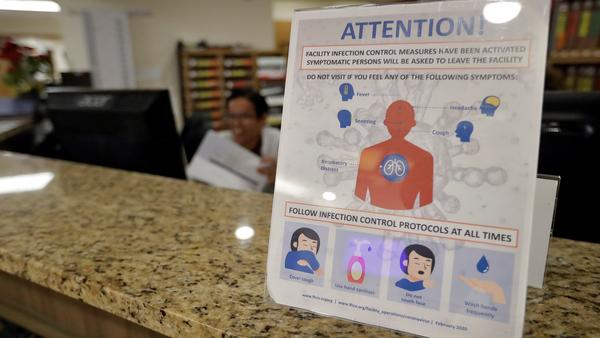 An infection Control Protocol poster sits on a nursing station desk at the Palm Garden of Tampa Health and Rehabilitation Center.