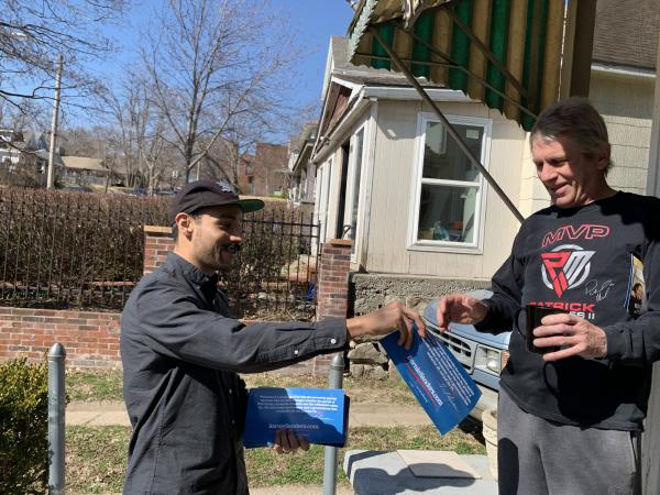 Ricardo Flores, a volunteer for Bernie Sanders, hands John Rellihan a campaign flyer in North Kansas City, Mo., on Sunday. Sanders' supporters are making a big push for him to regain front-runner status.