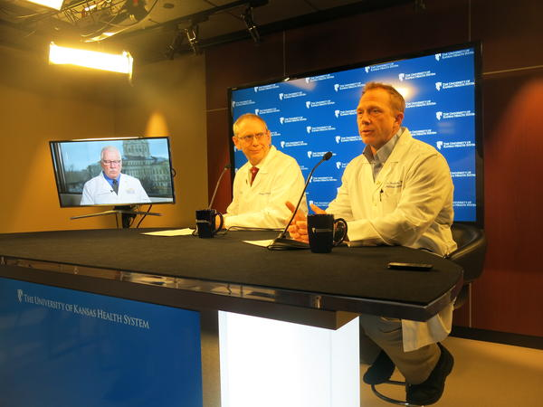 KU doctors Steven Stites (left) and Dana Hawkinson provide updates on a coronavirus patient admitted to the hospital. Kansas Director of Health and Environment Lee Norman is on the television monitor.