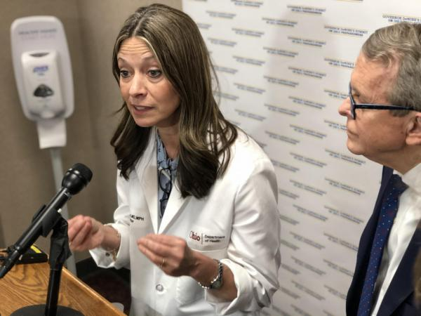 Dr. Amy Acton, with Gov. Mike DeWine alongside, talks to reporters before the statewide coronavirus summit.