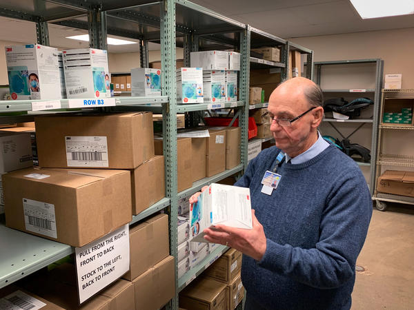Tom Cooper, Nashville General Hospital's supply chain director, inspects a box of N95 respirators. The hospital is among a small group of pilot sites now sharing data about the inventory of its protective equipment with the Centers for Disease Control and Prevention.