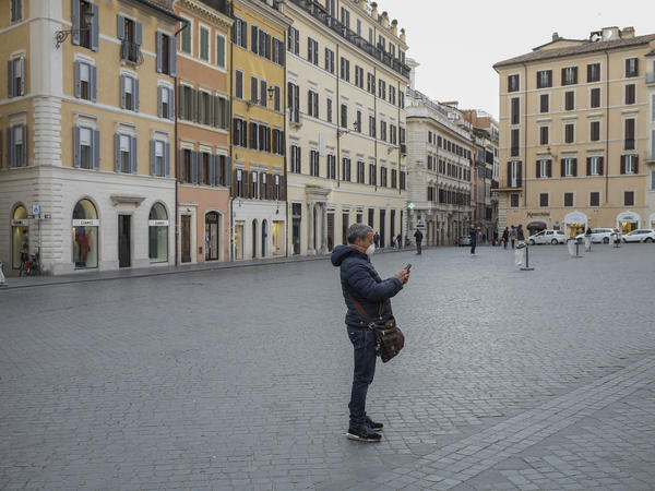 A person wearing a face mask at the Piazza Di Spagna in Rome during the coronavirus emergency, on Tuesday, after the Italian government imposed national restrictions to control the spread of the COVID-19 disease.