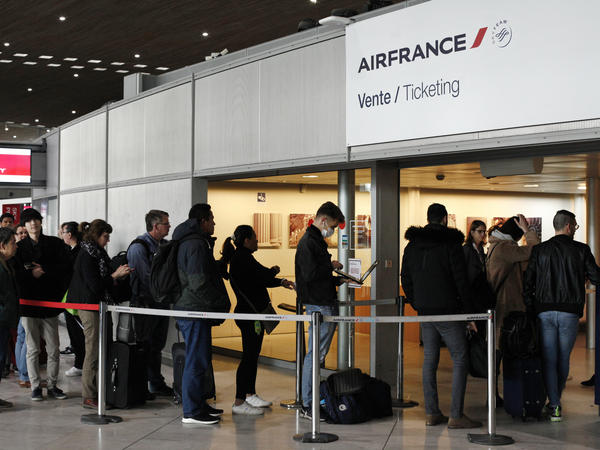 Passengers wait in front of the Air France desk at an airport near Paris on Thursday, a day after President Trump announced a 30-day ban on travel from most of Europe to the United States.